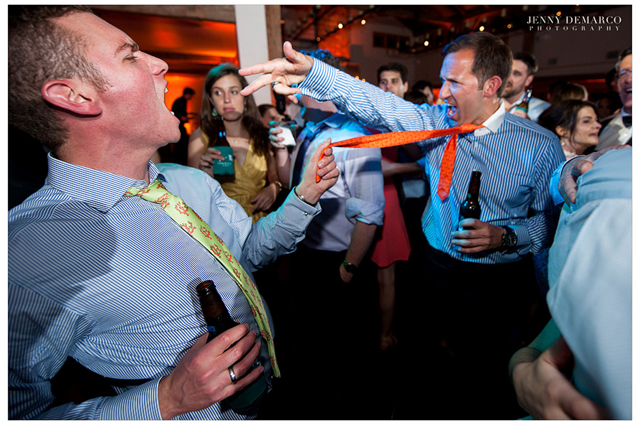 One man is pulling the other man's tie while dancing and having fun at the reception in the Ian's Chapel Events Hall.
