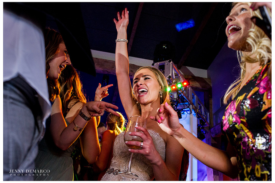 The bride is dancing with one arm up in the air while holding a wine glass in the other hand at the reception in the Ian's Chapel Events Hall.