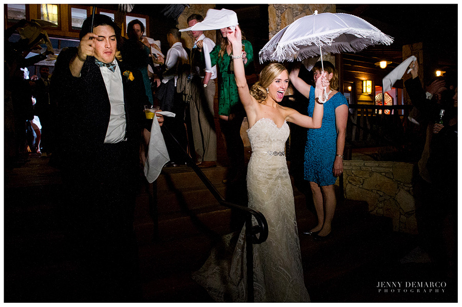 The bride and groom are doing one of the most popular traditions from New Orleans weddings, which is the famous Second Line where they hold an umbrella and a handkerchief while following the band. It signifies the start of a new beginning of life for the bride and groom.