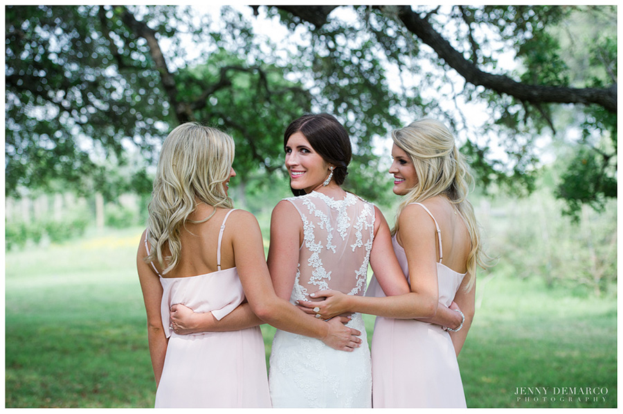 Bridesmaids and Bride posing for a picture at the Vineyards at Chapel Lodge featuring the back of Shelby's wedding dress.
