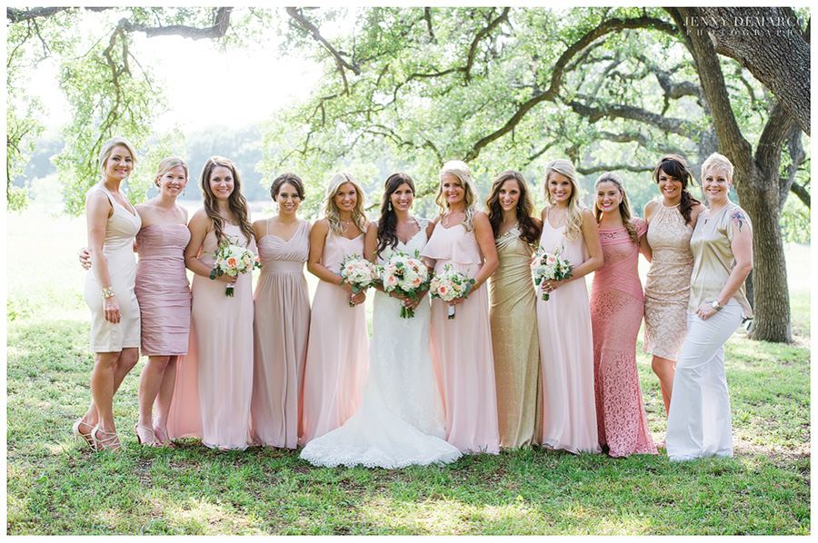 Bride, bridesmaids, and house party portrait showing off Shelby's romantic wedding colors in the vineyard.