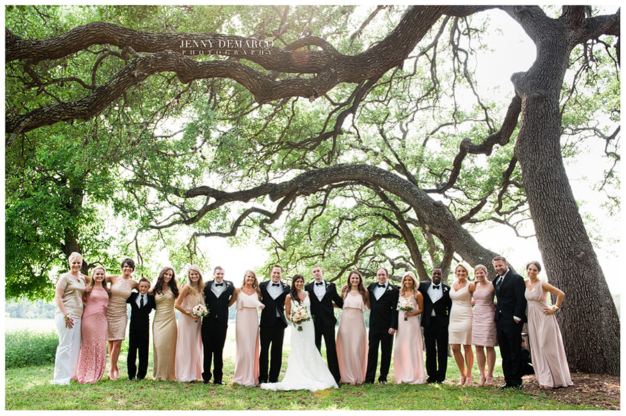 The bride and groom standing with their full bridal/house party under a Live Oak Tree in the charming venue.