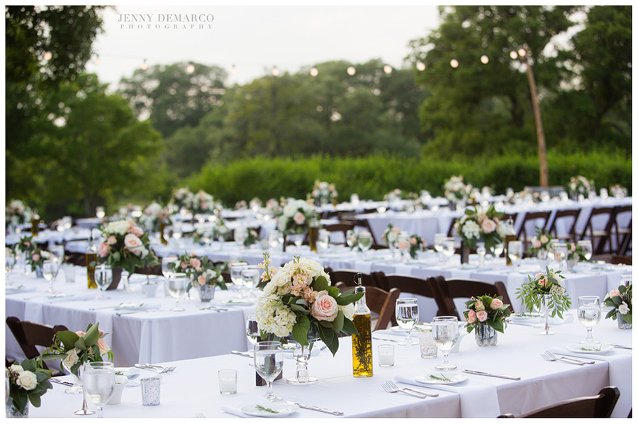 Connected banquet tables with reception decor and light colored flowers on top of them.