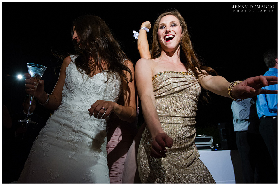 The bride, with martini in hand, and friend dancing at the wedding reception.