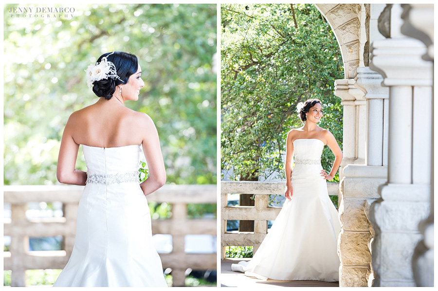 The bride has a beautiful hair style. It is an elegant side bun accessorized with a feathery flower hair clip. she is standing on a beautiful porch with an stone archway and columns.