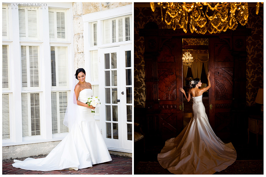 THe bride is holding her bouquet and looking down at the train of her wedding dress while standing on a brick pavement next to white doors with windows. the bride is standing in a cherry wood doorway showing off how long the train of her dress is.