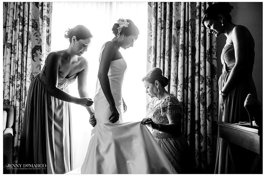 The mother of the bride and bridesmaids help Stephanie button up her wedding dress before the ceremony at Barton Creek Resort.