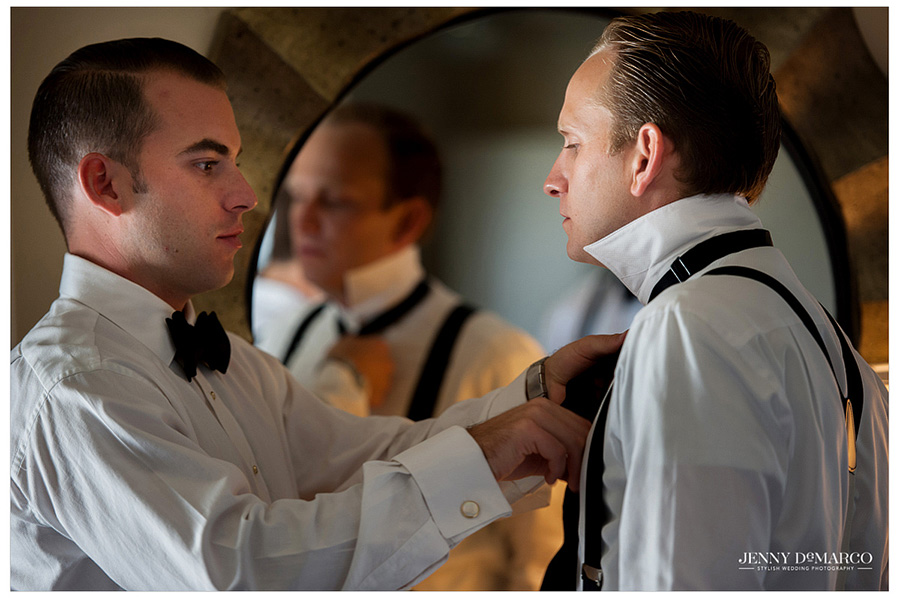 The groomsmen helping the nervous and excited groom tie his bow tie in preparation for the big day.