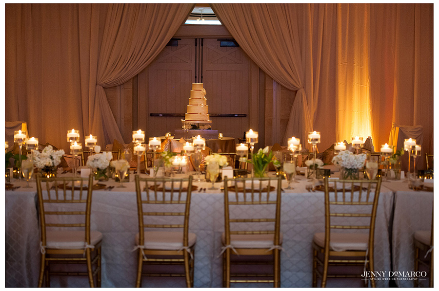 Situated next to the delicious wedding cake, the head table is beautifully decorated with florals and candles bring light and character to the wedding ballroom.