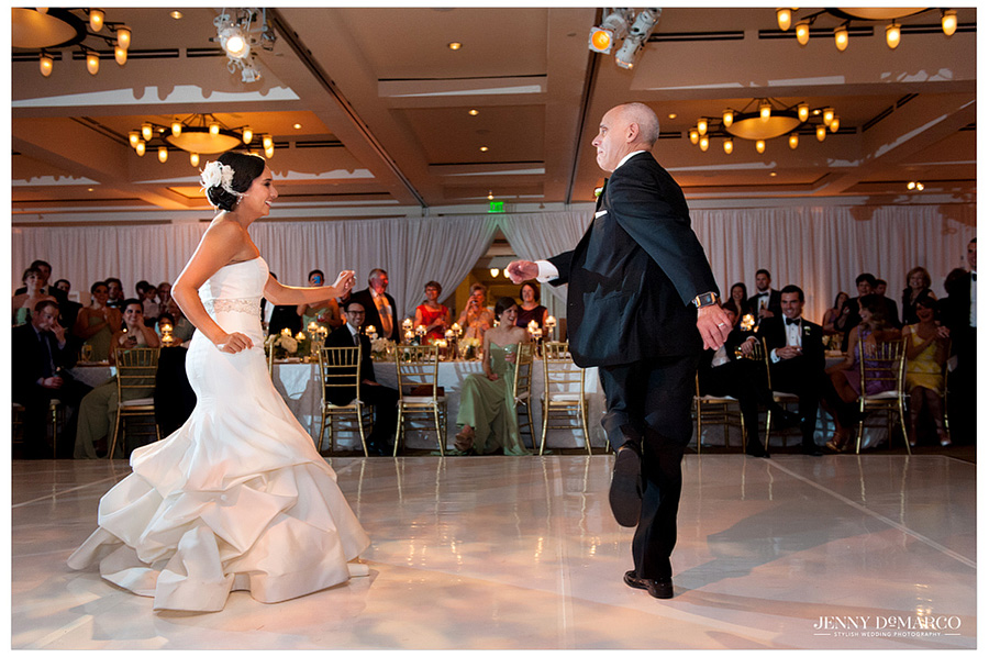 Stephanie and her dad begin the traditional father daughter dance with fun moves and laughter on the dance floor surrounding family and friends.