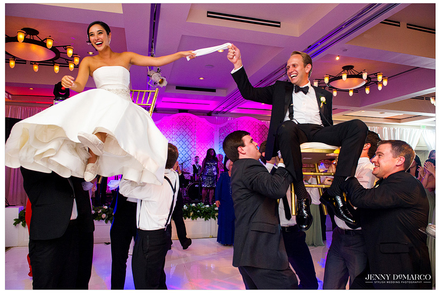 The Bride and Groom hold a napkin while being thrown into the air honoring and celebrating their Jewish heritage.