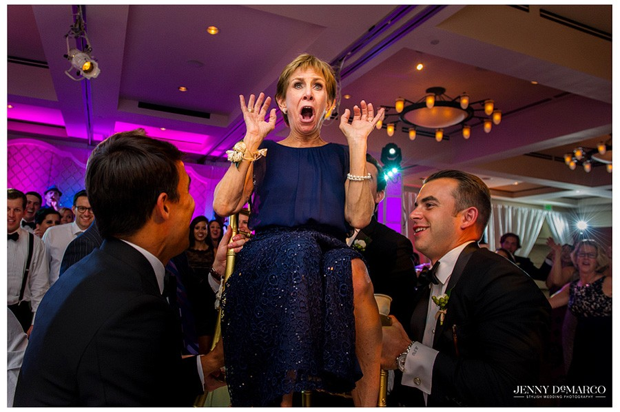 The groom's mother is shocked as she is lifted into the air as a Jewish Wedding tradition.