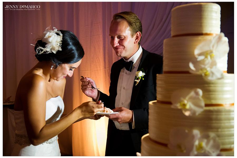 Stephanie and Sam feeding each other their wedding cake at Barton Creek Resort.