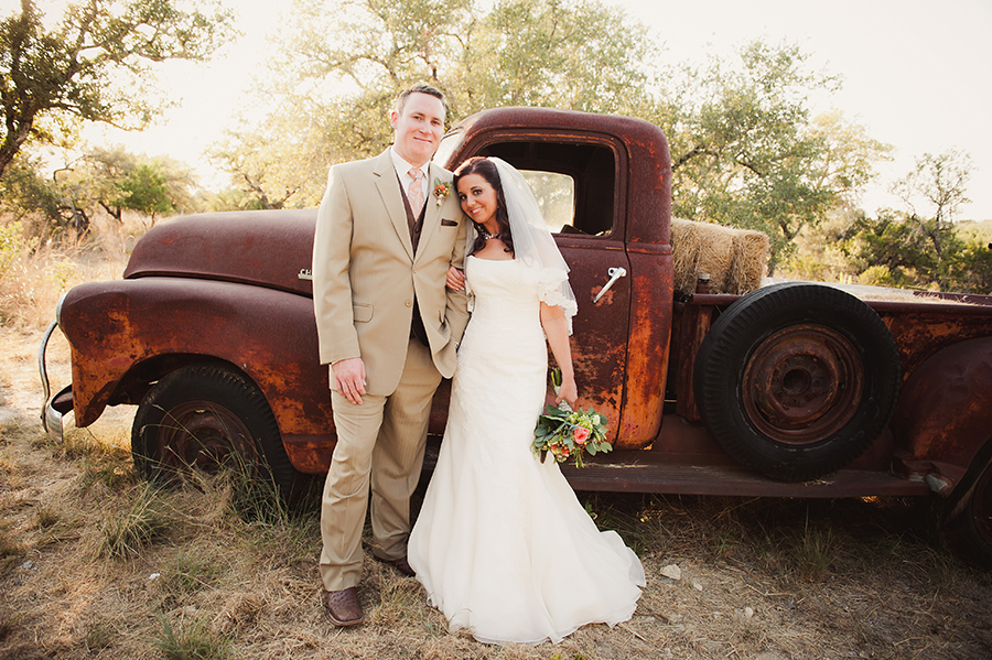 Bride and groom photographed in front of the rusted vintage truck parked in the fields.