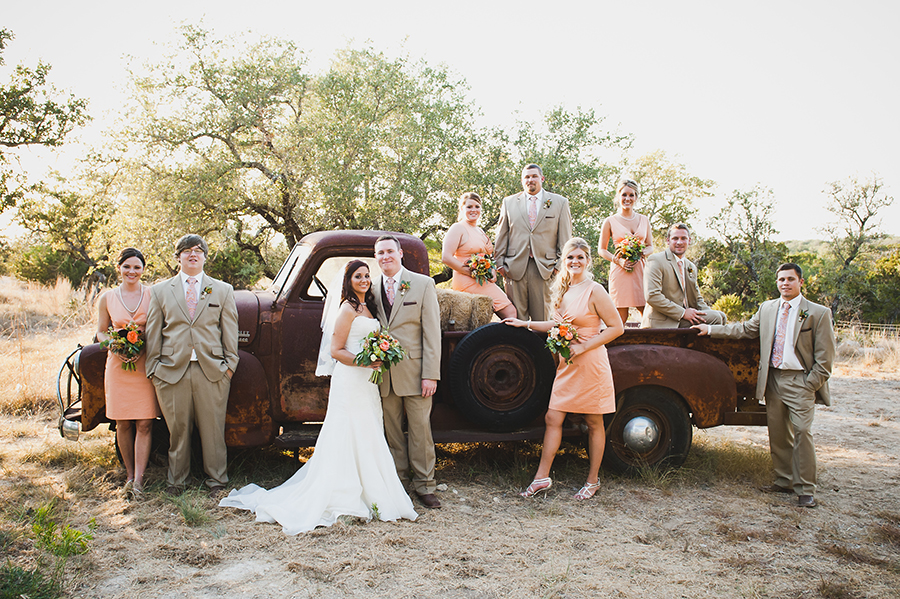 Bridal party photographed around a vintage truck parked in a field
