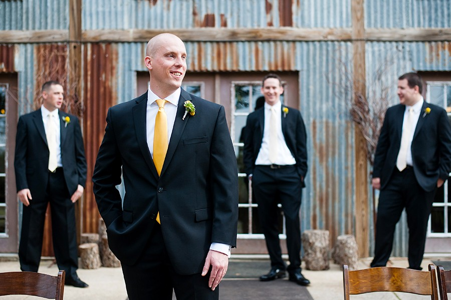Groomsmen portrait in front of the metal siding of the rustic barn