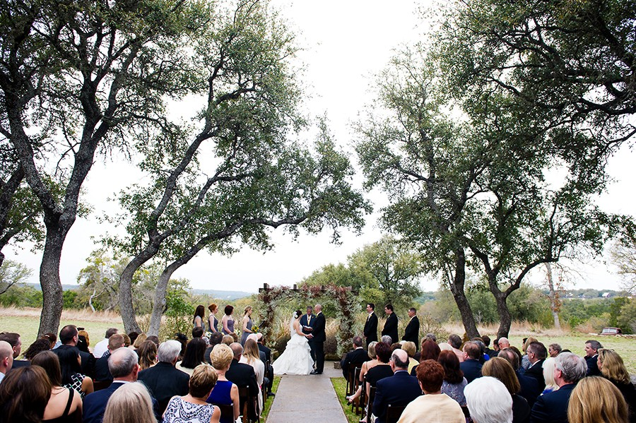 The wedding ceremony site takes place out side under the live oak trees in the texas hill country.