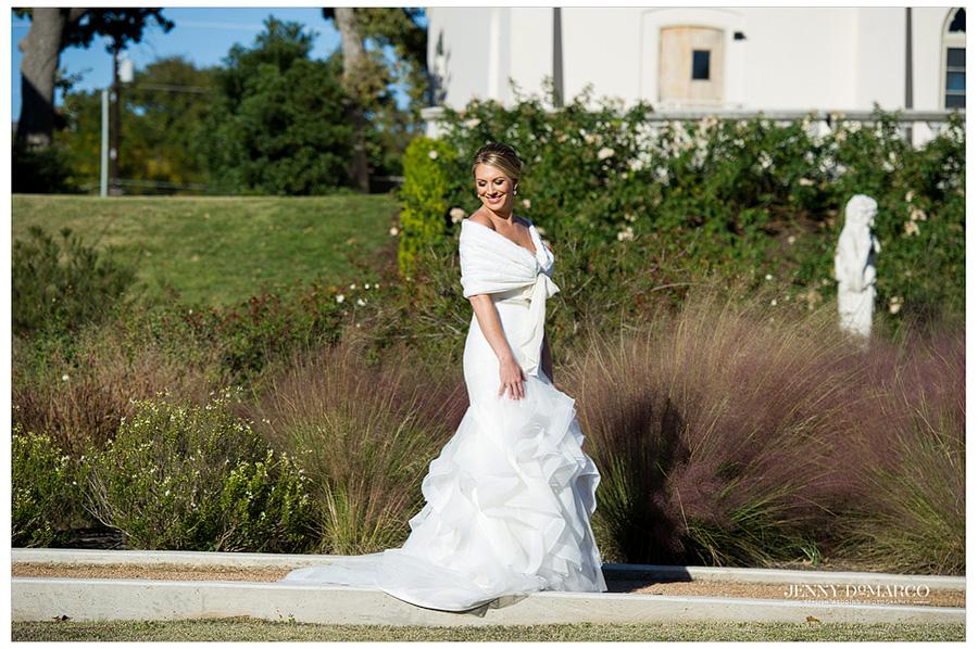 Bride walking through the mediterranean styled formal gardens.