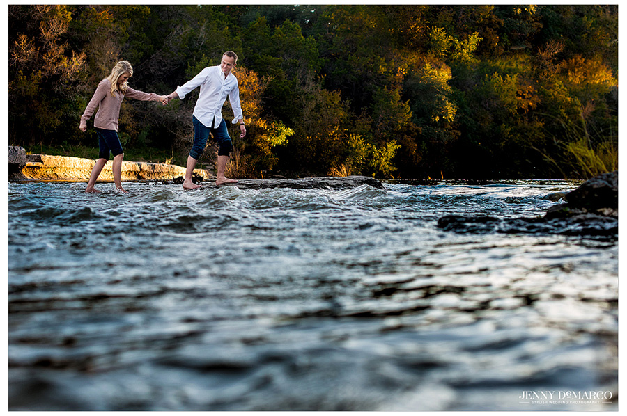 Groom leads his bride walking across the stream during their engagement session.