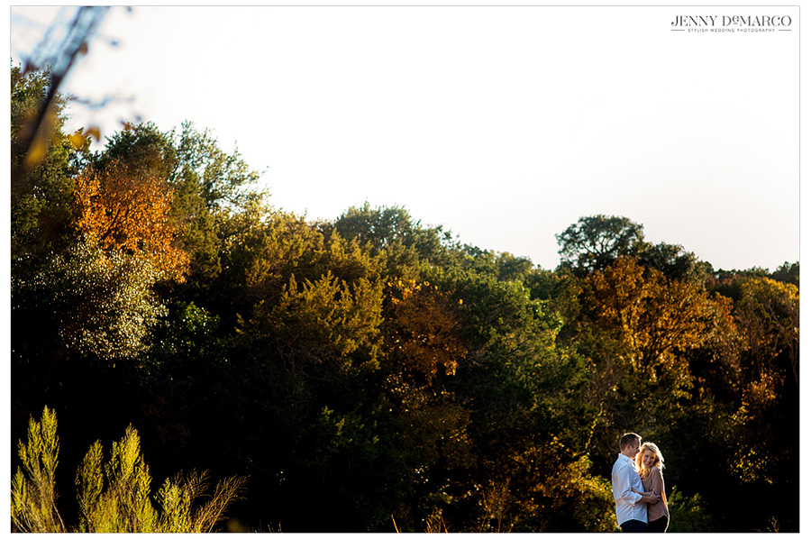 Bride and groom pose for their engagement portraits in front of the colorful fall foliage in the Texas Hill Country.