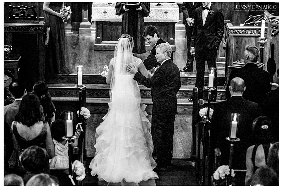 Black and white wedding photo of father giving away his daughter to the groom.