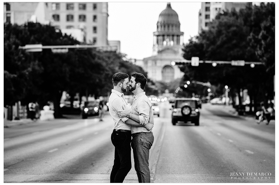 Gay men kiss with the Texas State capitol in the background.