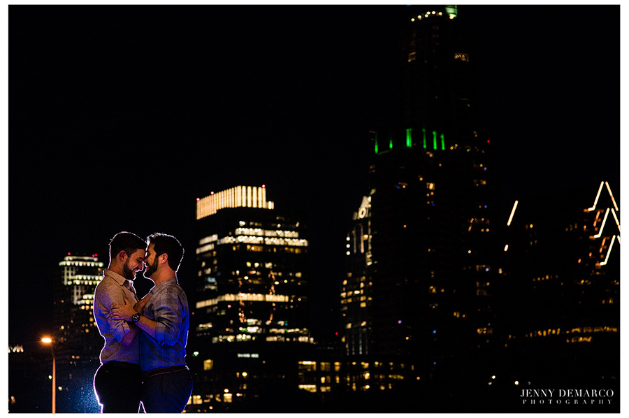 Gay couple poses for their engagement session with the downtown austin skyline in the background.