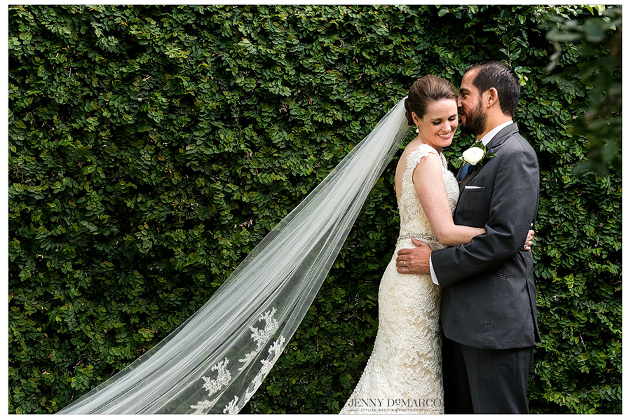 Gorgeous shot of bride and groom after exchanging vows in front of ivy wall.
