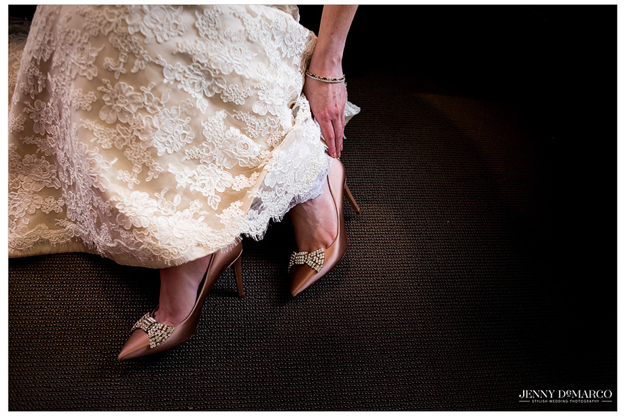 Great shot of bride putting on her gorgeous gold heels before walking down the aisle.