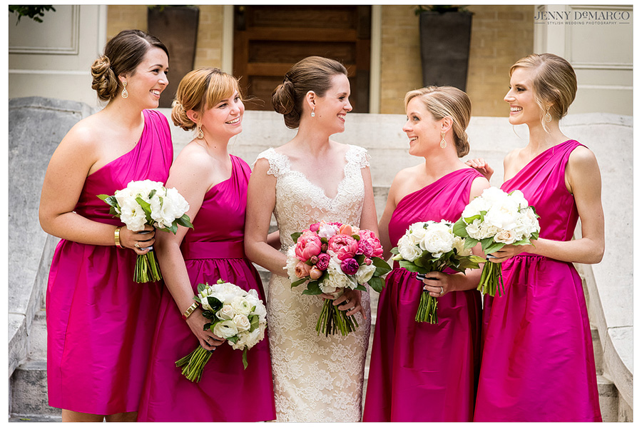 Smiling photo of bridesmaids in magenta with the bride before she walks down the aisle.