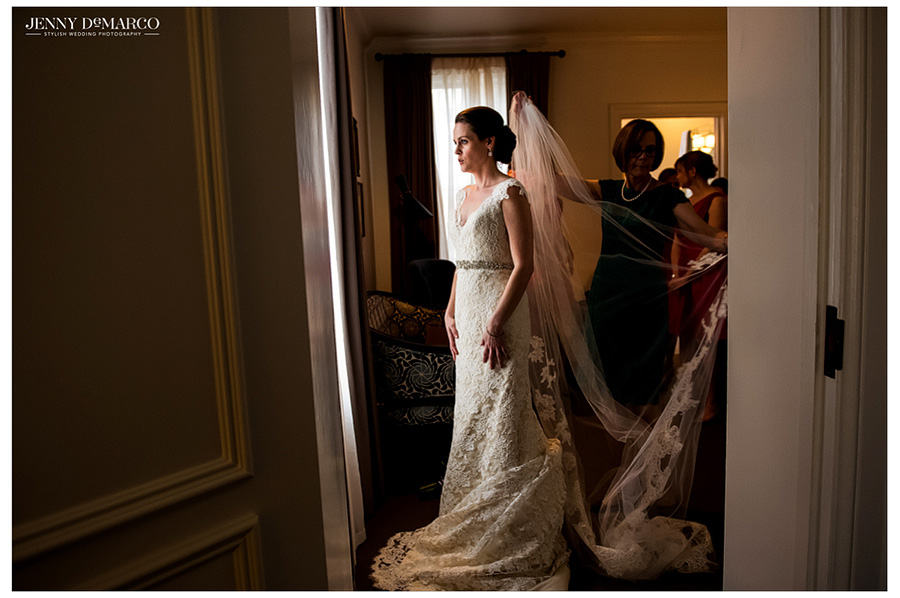 Intimate shot of last minute touches to the bride's gown before she walks down the aisle.