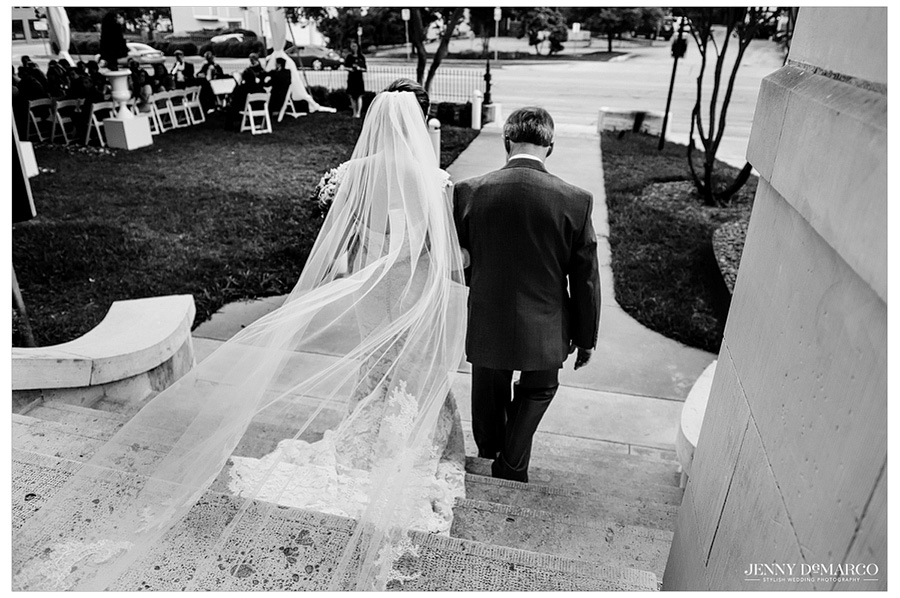 Black and white back shot of bride and her father walking down the steps towards the aisle.