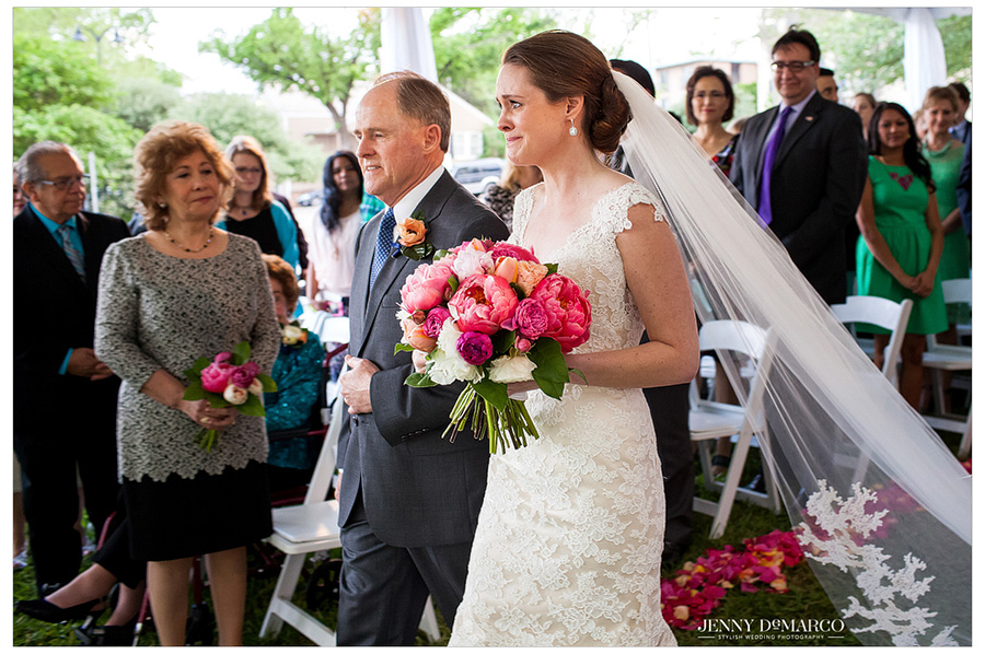 Bride walks down the aisle with her father, holding a gorgeous pink bouquet.