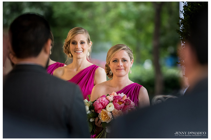 Wonderful shot of bridesmaids looking at the bride during the ceremony at Hotel Ella.