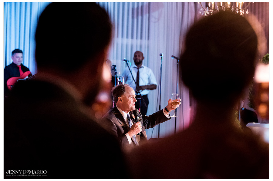 Unique shot of the father of the bride giving a toast during the wedding reception.