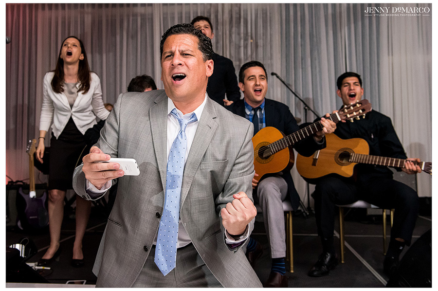Hilarious shot of wedding guests singing and dancing at reception.