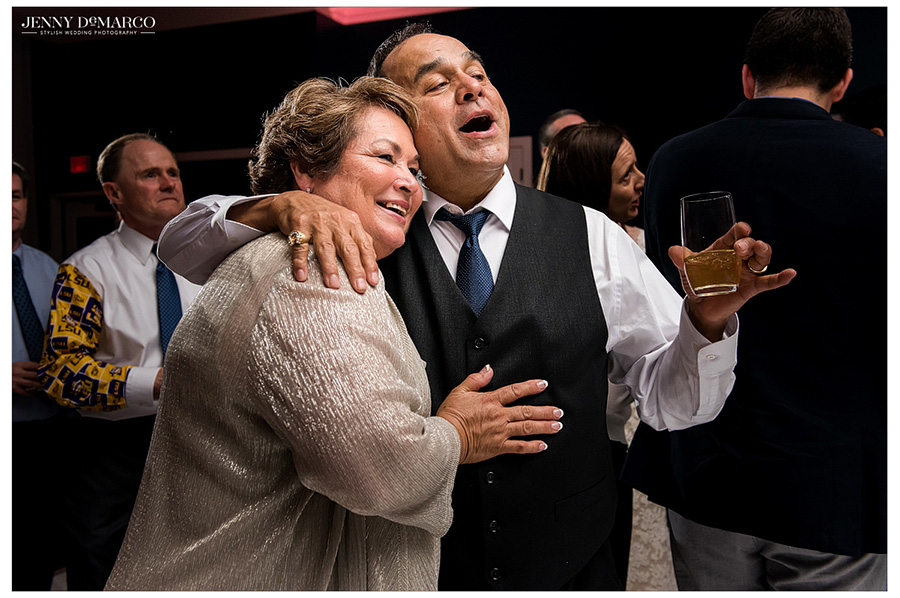 Parents of the groom hug and smile together on their son's big day.