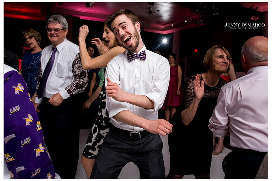 Wedding guest with LSU bowtie sings and dances at reception.