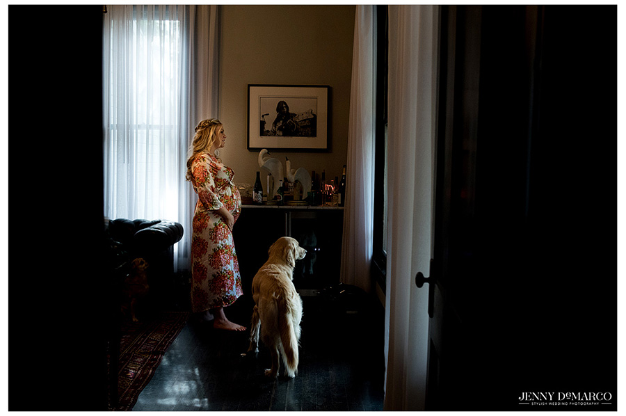 Bride and her dog stair out the window before putting on her dress.