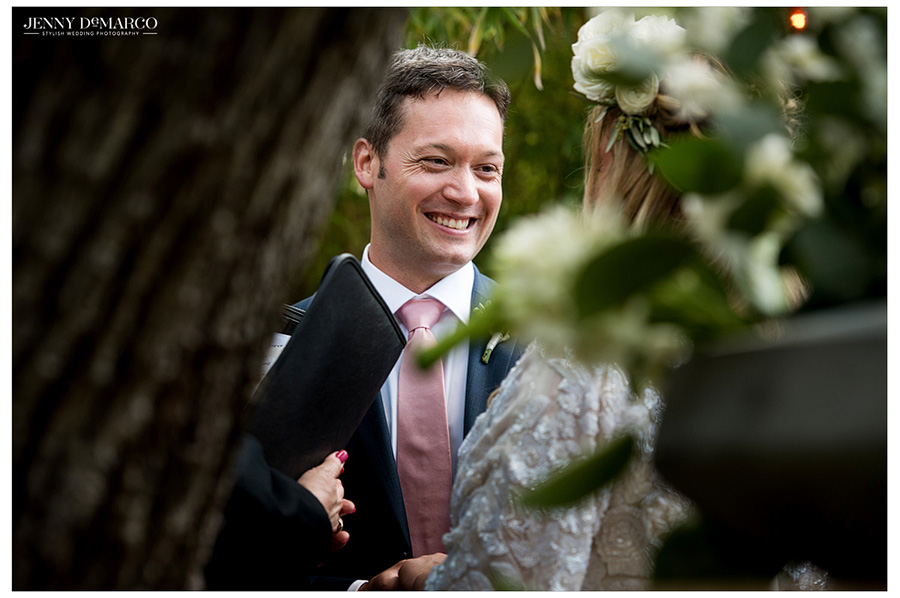 Groom in pastel pink tie smiles at his beautiful bride.