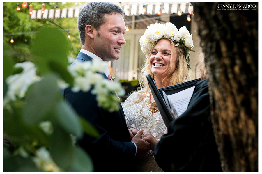 Pregnant bride, wearing gorgeous flower crown, smiles happily at her groom.