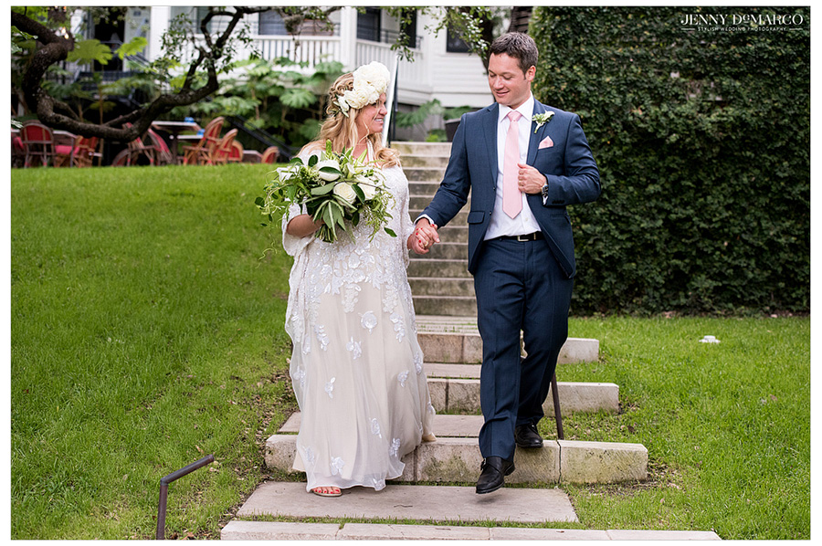 Pregnant bride and groom walk hand in hand down the steps after their shotgun wedding.