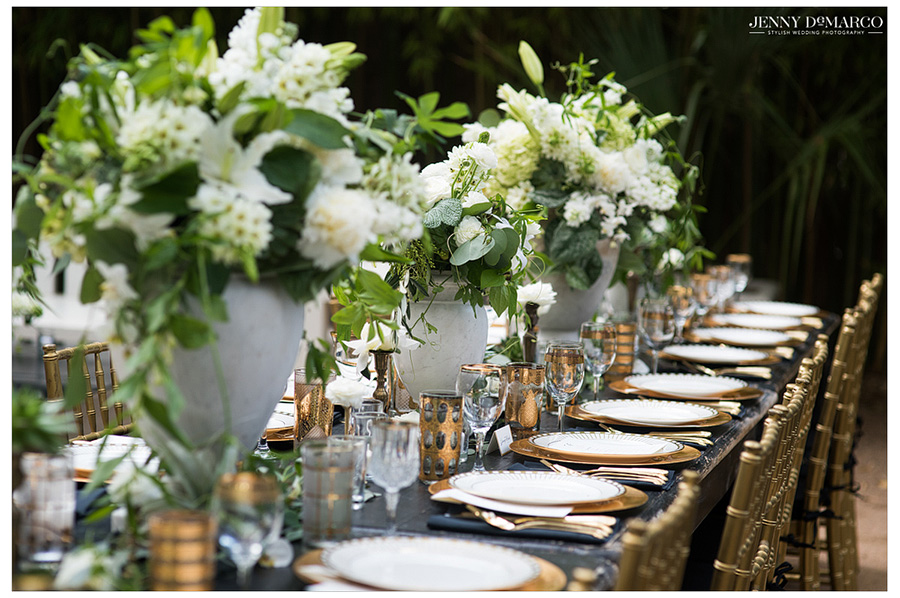 White and green florals line a beautiful outdoor wedding reception table.