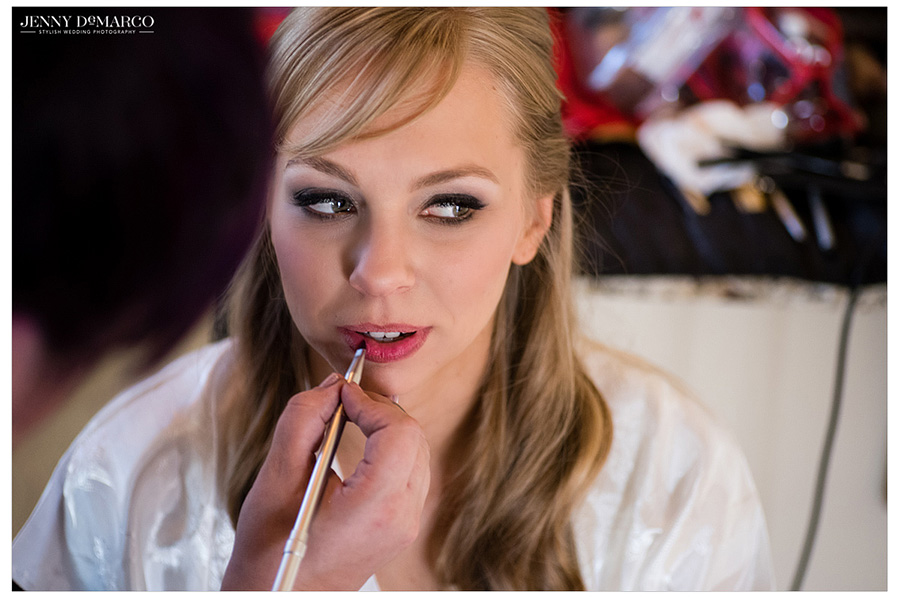 Bride gets her makeup done before walking down the aisle at her black tie wedding.