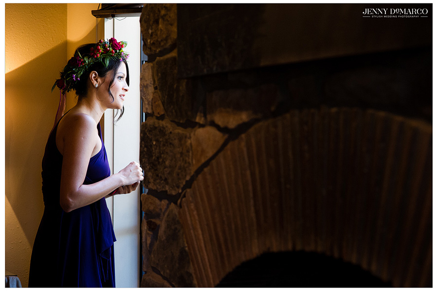 Bridesmaid in jewel tone gown looks out the window before the ceremony of a vineyard wedding.