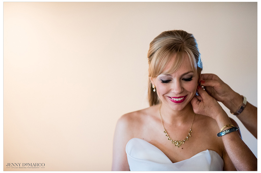 Gorgeous bride gets a beautiful pair of earrings put on her.