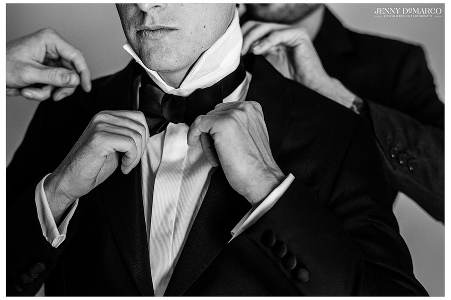 Awesome black and white shot of groom tying his bow tie before his vineyard wedding.