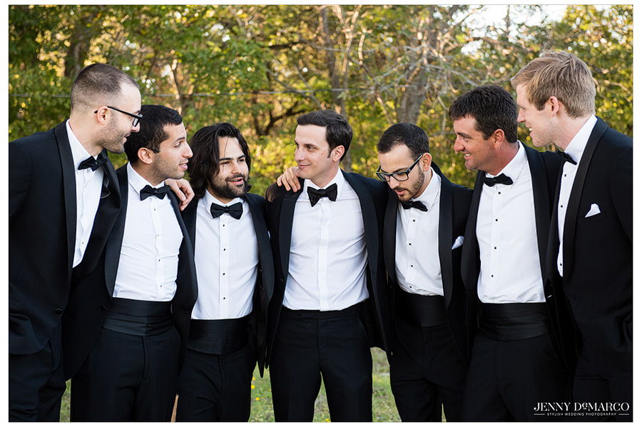 Groomsmen in black tie huddled together before the wedding ceremony.