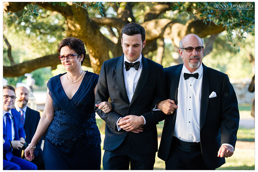 Jewish wedding tradition of groom's parents leading him down the aisle.