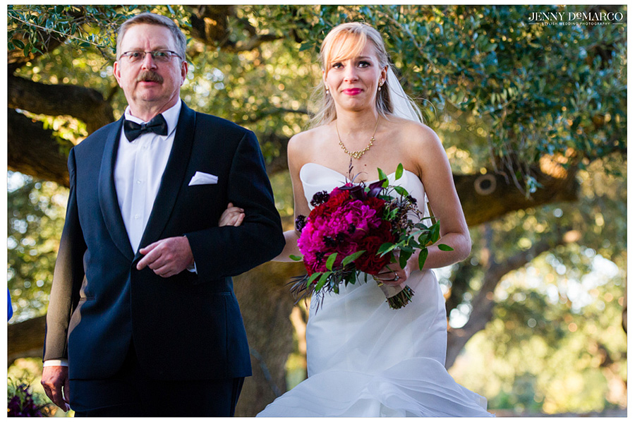 Priceless photo of bride walking down the aisle, arm in arm with father.